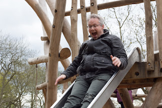 A daddy enjoying going down the slide