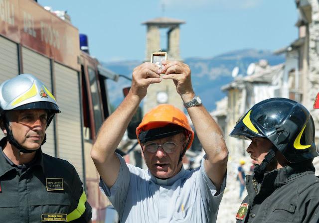 O padre Savino de Amatrice segura a 'Madonna de Filetta' delicadíssima imagem recuperada na igreja de Santo Agostinho inteiramente destruída