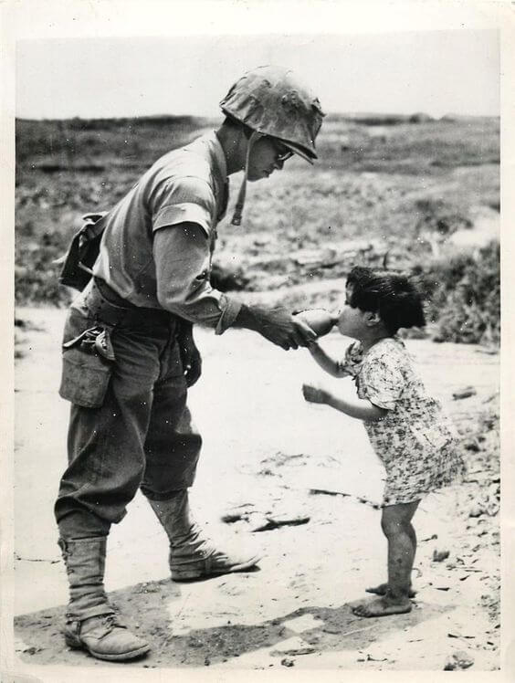 12 Powerful Images That Prove There's Still Kindness In The World - This US marine is offering water to a Japanese girl he discovered in a cave. (1945, Okinawa)