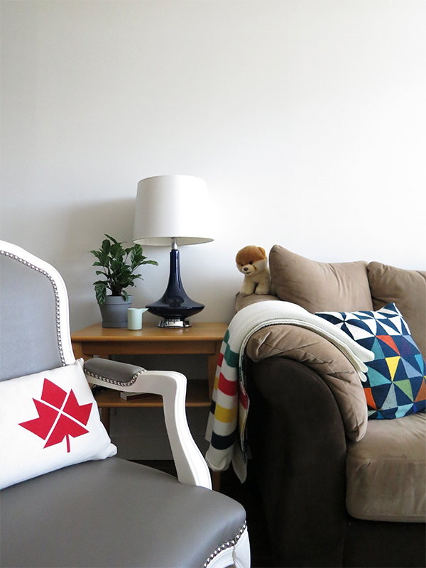 A Mt. Pleasant, Vancouver, condo living room mixes eclectic elements—primary colours, warm neutrals, rich textures, mid-century modern and contemporary furniture pieces, handicrafts-inspired pillows—to create a warm, inviting, cozy space.