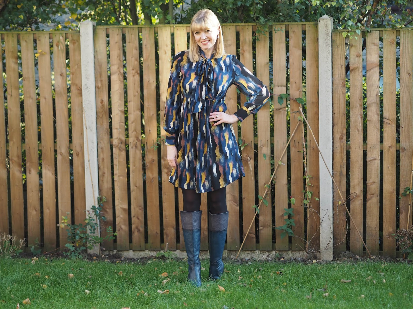 Tie neck print smock dress with pussy bow, and navy knee high boots with black cuff, over 40