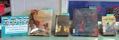 Countertop display of books with sign: '2019 American Library Association / Youth Media Awards / Winners and Honor Books.' The books, arranged with front-covers facing forward, are, left to right: 'Dreamers' by Yuyi Morales, 'The Truth According to Mason Buttle' by Leslie Connor, 'The Stufff of Stars' by Marion Dane Bauer, and 'Merci Suarez Changes Gears' by Meg Medina.
