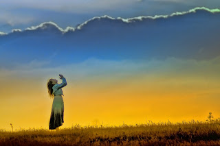 Girl with hands raised in worship against a sunset