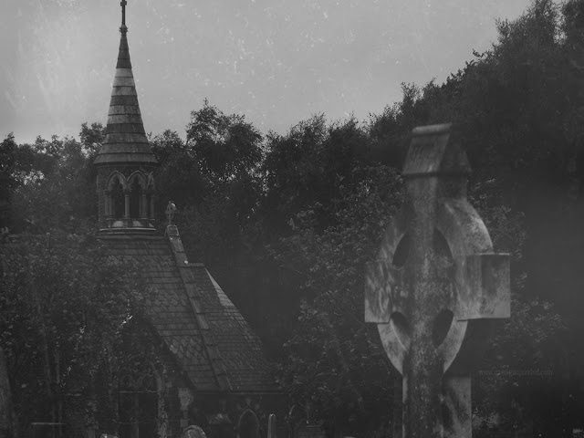 black and white photo of grave stones and a church