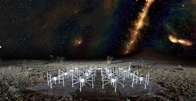 A 'radio color' view of the sky above a 'tile' of the Murchison Widefield Array radio telescope, located in outback Western Australia. The Milky Way is visible as a band across the sky and the dots beyond are some of the 300,000 galaxies observed by the telescope for the GLEAM survey. Red indicates the lowest frequencies, green the middle frequencies and blue the highest frequencies. Credit: Radio image by Natasha Hurley-Walker (ICRAR/Curtin) and the GLEAM Team. MWA tile and landscape by Dr John Goldsmith / Celestial Visions.