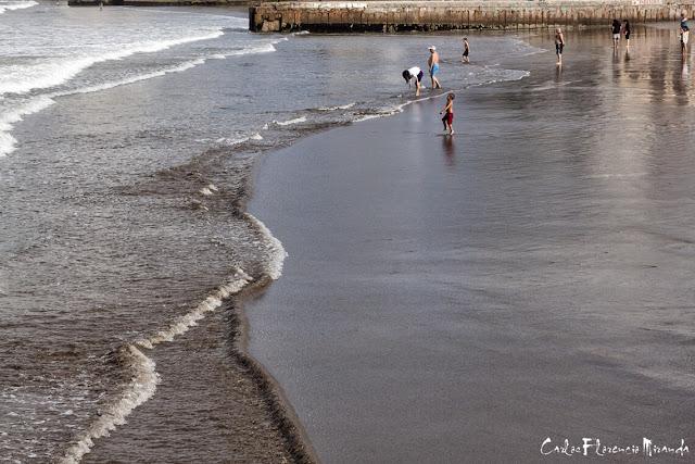 El mar llega a la playa y gente disfrutando .