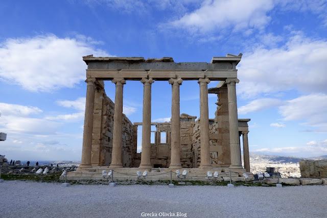 Na tle nieba gdzieniegdzie pokrytego chmurami widnieje zabytkowa świątynia Erchtejon Akropol, Ateny, Grecja