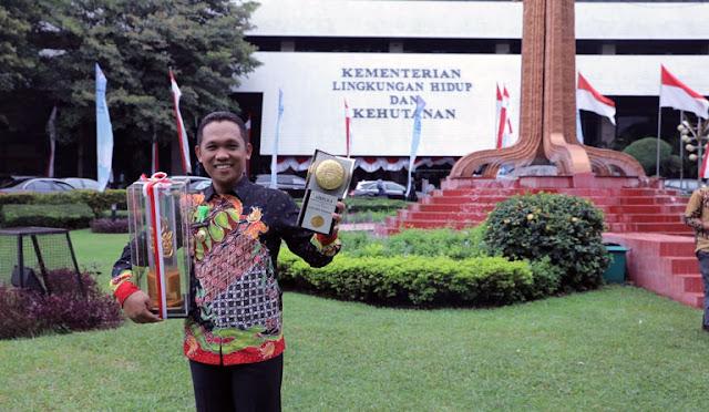 Bupati memegang dua piala penghargaan yang berhasil diraih Lumajang