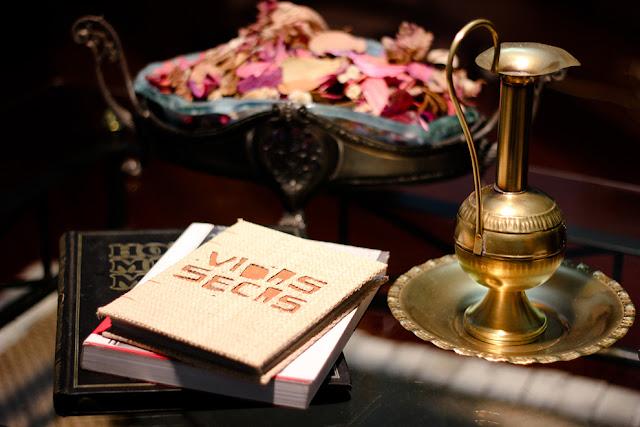 Imagem do livro em uma mesinha junto com outros livros empilhados.