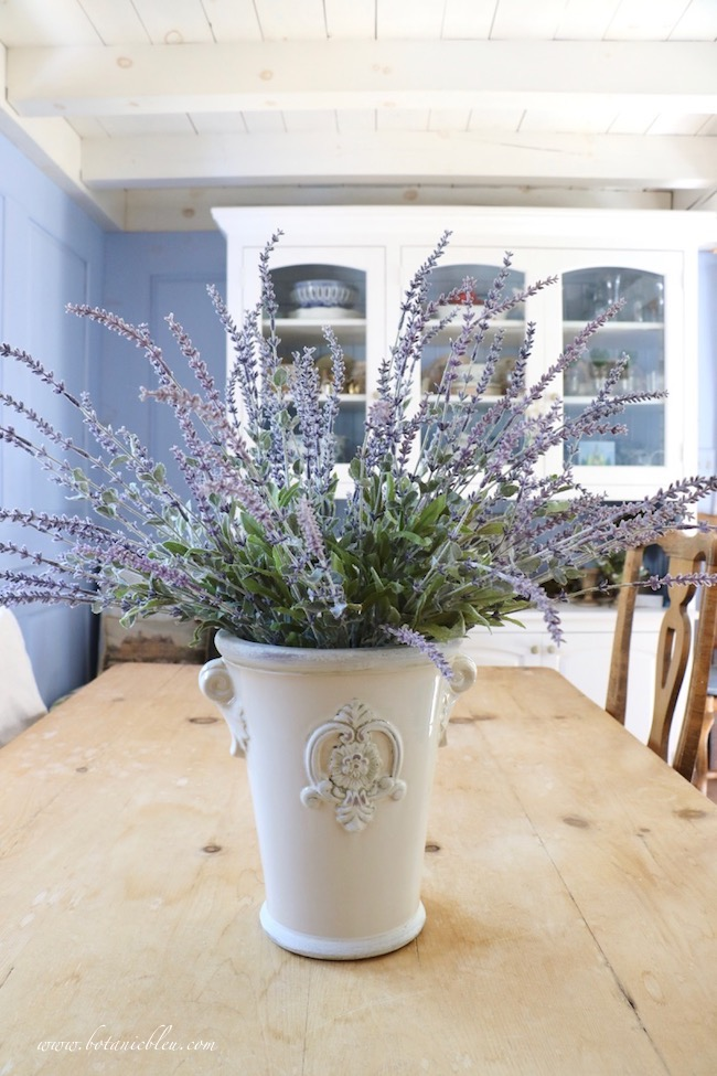 Faux French lavender in a French style ceramic pot on the vintage pine dining table