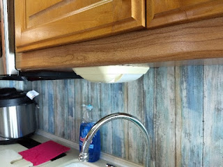 older rv light fixture mounted under a wood cabinet and over a kitchen sink spigot