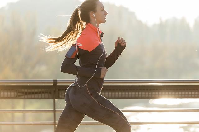 Une femme est en train de courir avec des écouteurs.