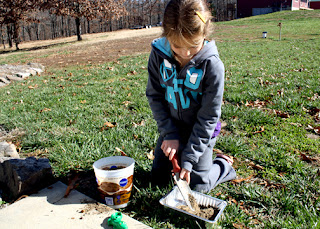 Tessa began by scooping a mixture of sand and dirt into a small disposable pan.