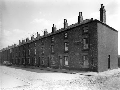 A greyscale picture of a long row of three story terraced houses.