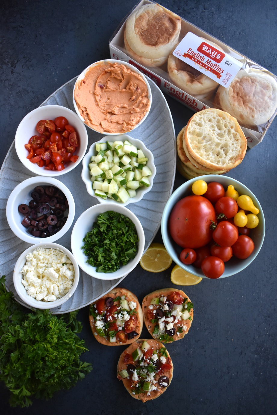Mediterranean Hummus Bites are loaded with red pepper hummus, kalamata olives, tomatoes, cucumber and feta cheese on a toasted English muffin for an easy appetizer ready in 10 minutes that everyone will love! www.nutritionistreviews.com #healthy #appetizer #cleaneating #holidays