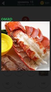 На поверхности стола лежит приготовленный омар и рядом блюдце желтого цвета