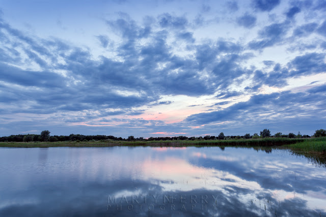 Sunset colours reflect in the calm waters at Ouse Fen by Martyn Ferry Photography