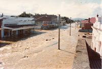 Brown flood waters on Otautau's Main Street, BNZ and drapery buildings