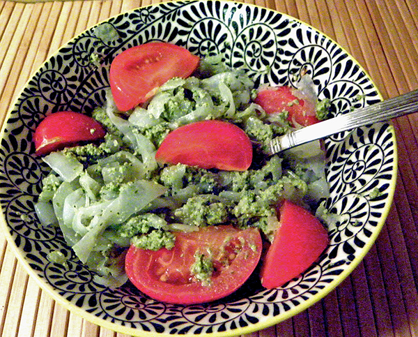 Pesto mixed into noodles and tomatoes