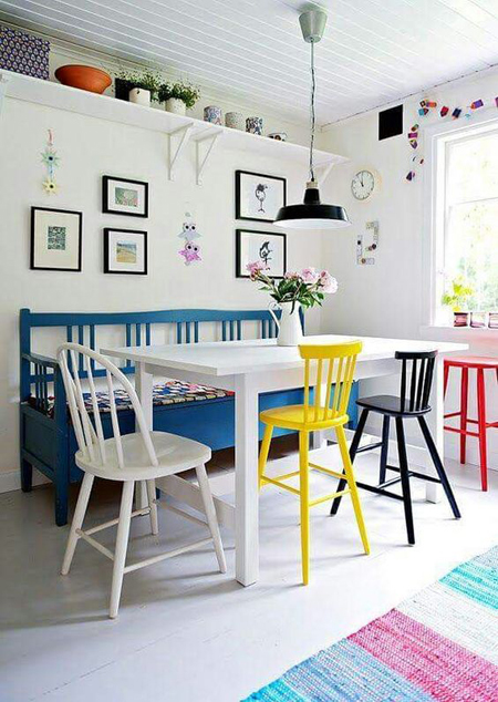 mesa moderna com cadeiras coloridas e banco de madeira pintado de azul