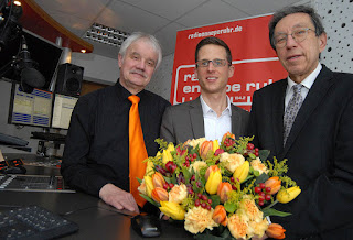 Einen bunten Frühlingsstrauß bekam Andreas Wiese von den VG-Vor-standsmitgliedern Peter Dziadek (rechts) und Michael A. Winkler zu seinem Start als CR überreicht. Dziadek und Winkler waren selbst vor 39 Jahren ehrenamtlich beim Krankenhausfunk Witten aktiv. (Foto: Barbara Zabka)