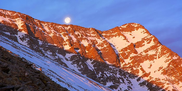 The full moon sets over Marble Mountain as the sun rises to the east