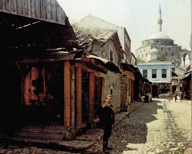 Perspective on an alley of the old shopping district. In the background, the mosque of Mustafa Pasha (15th century), photographed on the southeast side. In the foreground, an open type shoemaker shop. Instead of walls, the shop has shutters that are closed and opened as needed. The alley is paved with stones, with a gutter in the middle. - Macedonia in 1913