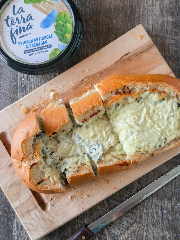 This Spinach Artichoke Stuffed Cheese Bread is the perfect appetizer for game day! Creamy dip gets stuffed into a loaf of fresh bread, topped with shredded mozzarella, then baked to cheesy perfection.