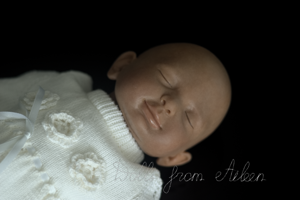 hand sculpted clay baby girl smiling in her sleep