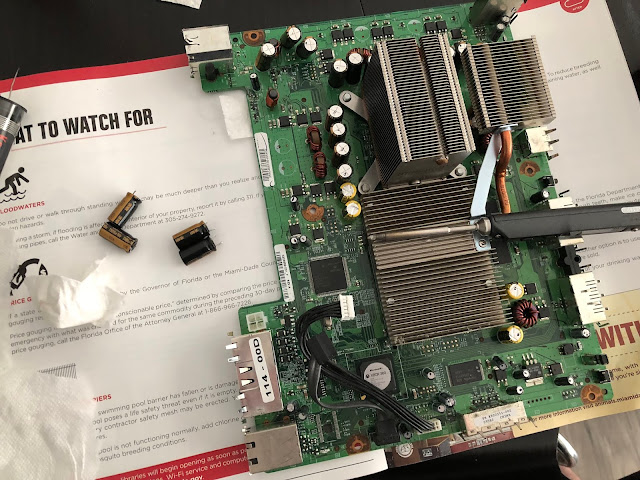 an Xbox 360 main board, with a soldering iron on top of it and several capacitors next to it