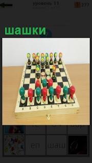 На шахматной доске установлены необычные фигурки шашок, в виде матрешек и лампочек