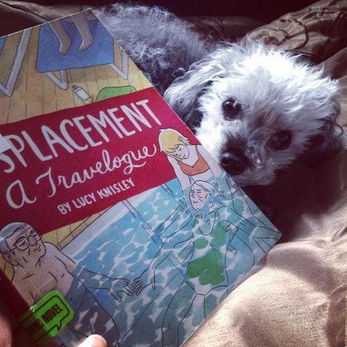 Murchie peeks out from around a paperback copy of Displacement. Its cover features a ginger white girl supporting a very old white woman in a small swimming pool while a very old white man looks on.