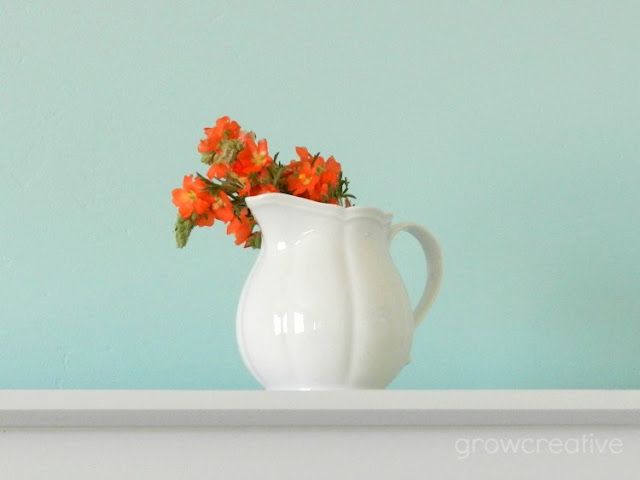 Orange Wildflowers in a white vase, blue and orange home decor: growcreative
