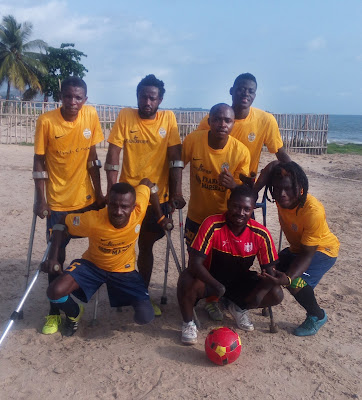 The Flying Stars amputee soccer team posing on Aberdeen Beach in Freetown