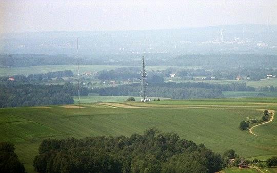 """Wielki Dział (377 m n.p.m.), a za nim Mały Dział (366 m n.p.m.) z niższym masztem antenowym. W dali po prawej widać Budynek szybu KWK """"Janina"""" w Libiążu."""