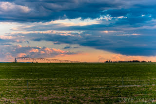 Cramer Imaging's fine art landscape photograph of a cloudscape at sunset over a farm field with irrigation equipment in Burley Idaho