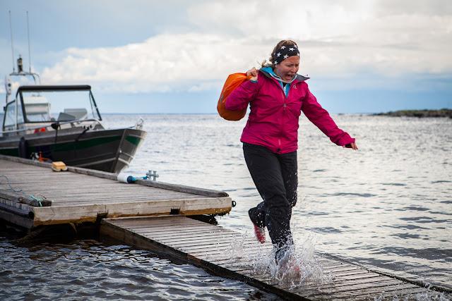 Nainen irvistää ja juoksee vesi pärskyen laiturilla, joka on puoliksi veden alla