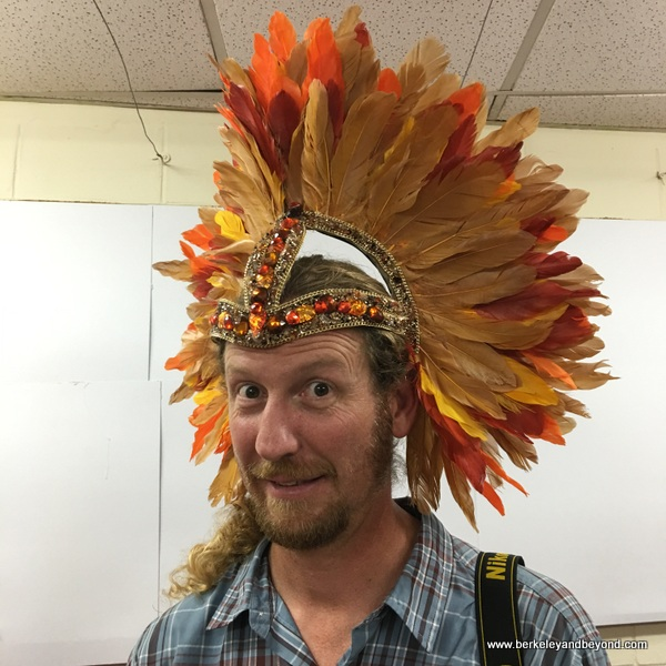 travel photographer Chad Case models feather headpiece at Ronnie of Ronnie & Coro Mas Camp costumes in Port of Spain, Trinidad