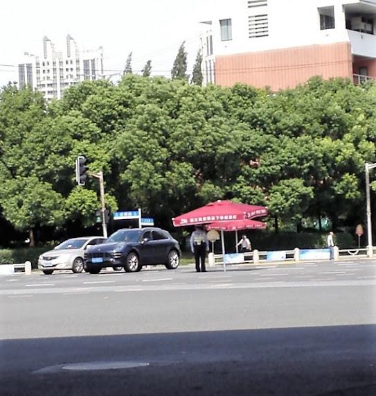 上海の古北地区にある巨大な交差点で交通整理をする警官がパラソルの下にいる