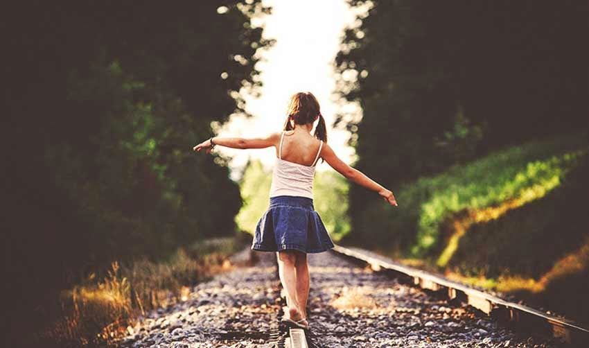 Cute Girl Walking on Rail Path