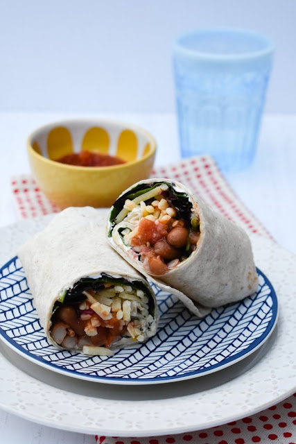Spicy Bean Lunch Wrap rolled and cut in half on a blue and white tea plate