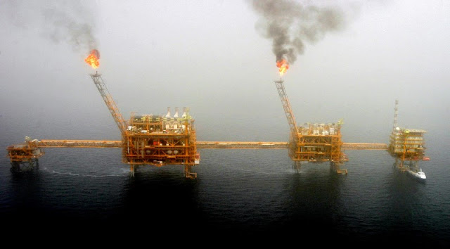 Gas flares from an oil production platform at the Soroush oil fields in the Persian Gulf, south of the capital Tehran, July 25, 2005.  REUTERS/Raheb Homavandi/File Photo