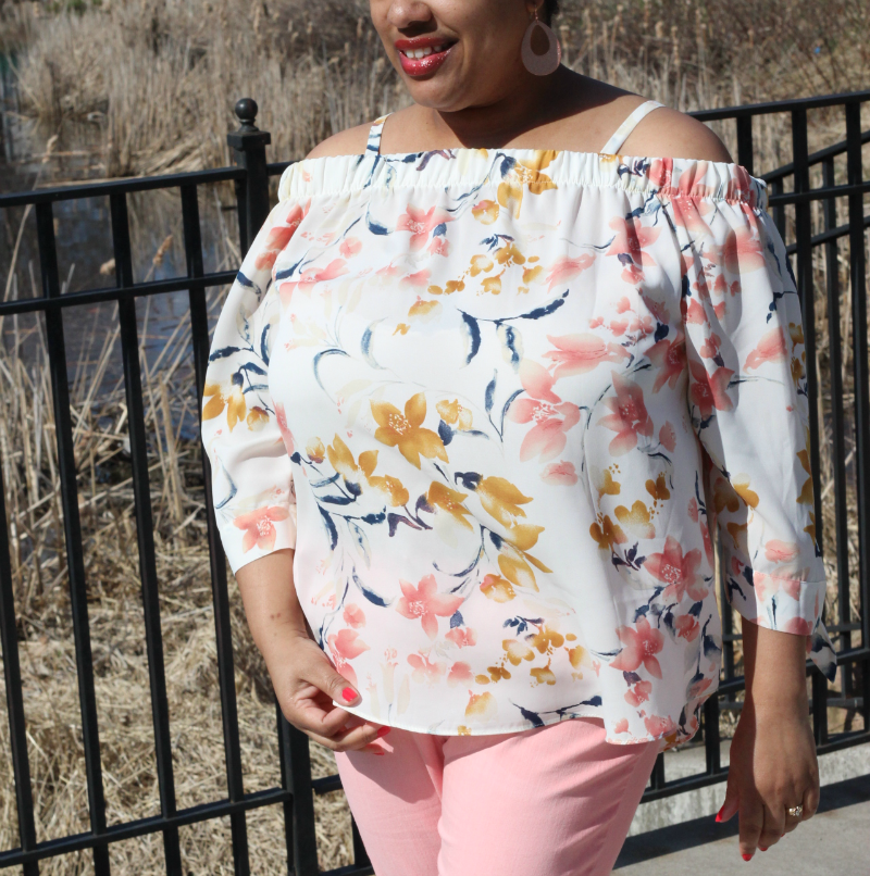 a woman wearing a floral off the shoulder blouse