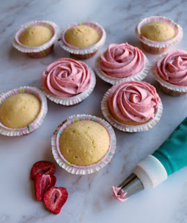 vanilla cupcakes getting strawberry buttercream piped on