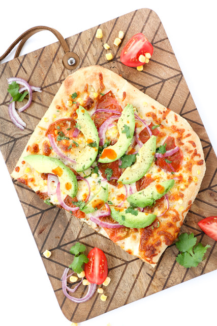Vegetarian Roasted Corn and Avocado pizza with fresh Heirloom Tomatoes, red onion, and Cholula with an Avocado Cream Sauce - The new Cinco De Mayo Party Food Recipe