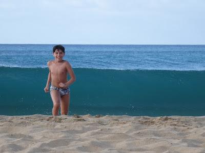 Crianças se divertem com as ondas imensas na praia da Conceição