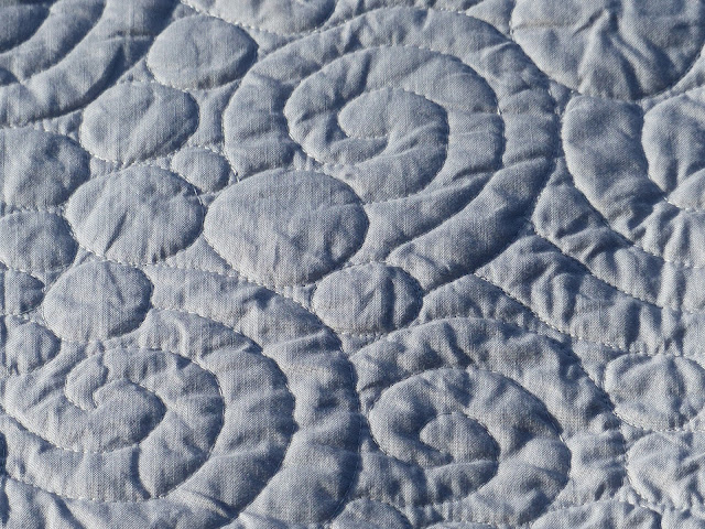 Close up view of a swirl and pebble quilting motif