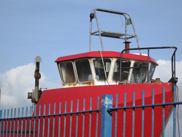 Old red fishing boat behind bright blue railings.