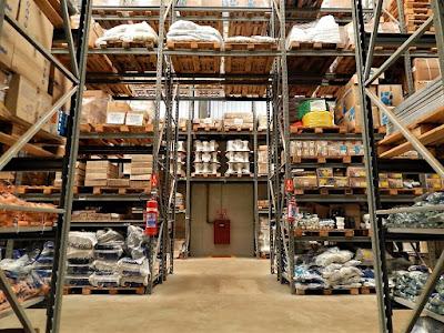 Grandes prateleiras metálicas trabalham em conjunto com paletes de madeira para estocar diversos produtos, sem interferir nos equipamentos de prevenção e combate a incêndios.