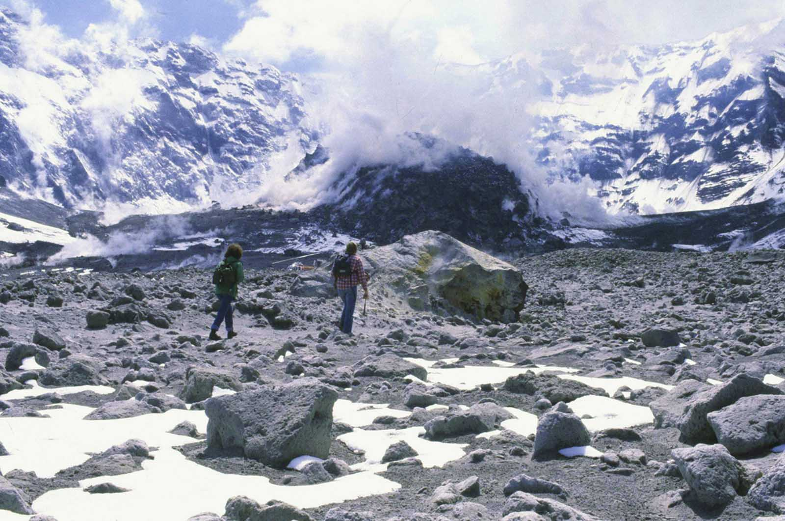 A Washington state geologist and a reporter walk toward the crater of Mount St. Helens in May of 1981, almost a year after the volcano exploded, causing dramatic destruction for miles around. They were near the steaming lava dome with the snow-covered crater wall beyond.